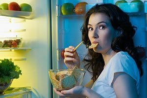 woman eating in front of open fridge