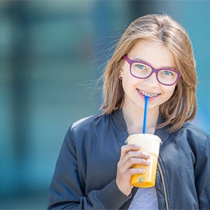 preteen with braces holding drink